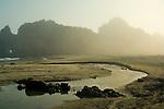 Stream flowing through sand below coastal rocks and fog at sunset, Pfeiffer Beach, Big Sur Coast, Monterey County, California