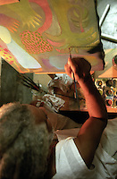 Manuel Mendive works on a piece in his home in Cuba in 1998. Many call him the island's foremost living artist. Art lovers in Cuba and abroad are fascinated with his brightly coloured sculptures and paintings, nearly all dedicated to Santeria, the Afro-Cuban belief system blending Roman Catholic saints and Yoruba deities.