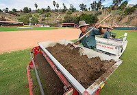 "Facilities staffers Jesse Montanez and Russ Jirel spread what used to be part of the Dodgers Stadium outfield onto the upper and lower soccer fields and part of Anderson Field on Wednesday. Ruben Campos, Oxy's assistant director of maintenance, knows the Dodgers' head groundskeeper and jumped at an offer to use the shredded combination of sod, soil and sand as a top dressing for the fields. (The stadium grass needed to be replaced after AC/DC's Sept. 28 concert.) ""It was so rich, it starting growing grass in the parking lot,"" said Campos. ""And it was free.""<br /> (Photo by Marc Campos, Occidental College Photographer)"