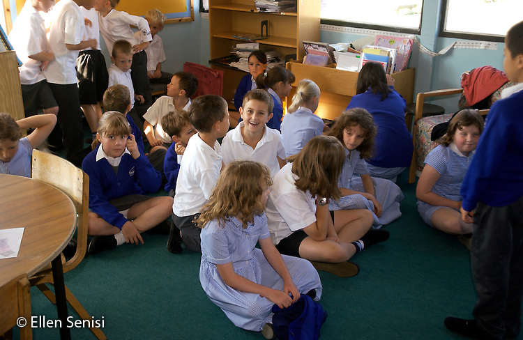 MR / Abingdon, Oxfordshire, England.Thomas Reade Primary School.Year 3/Year 4 mixed class, mainstreamed inclusion classroom.Students (aged 8-9, with uniforms) sit on floor talking, waiting for school day to begin. All Year 4 students in this class are on S.E.N. Report (Special Educational Needs)..©Ellen B. Senisi