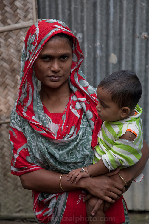 One of Shahnaz Hossain Begum's neighbors with her child in Bari Majlish village outside Dhaka, Bangladesh.   (Shahnaz Hossain Begum is featured in the book What I Eat: Around the World in 80 Diets.) Shahnaz, a mother of four, got her first micro loan several years ago, from the Bangladesh Rehabilitation Assistance Committee (BRAC) to buy cows to produce milk for sale. She was able to earn enough to build several rental rooms next to her home. She and her family don't drink the milk that helps provide their income. MODEL RELEASED.