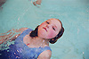 Young girl with complex congenital heart disease swimming in public swimming pool,