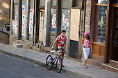 A girl and a boy with a bike walk past a closed business in Veliko Tarnovo. Although a popular tourist destination, the town has suffered as a result of the financial crisis.