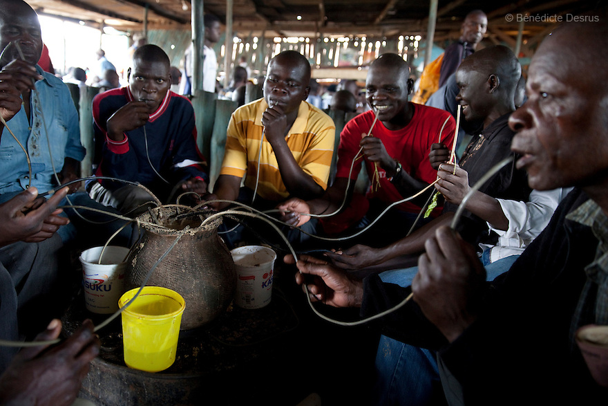 A group of Kenyans drink Busaa, a traditional fermented beer, from a common pot using long straws - in a crowded Busaa club at midday in a Nairobi slum on April 7, 2013. Busaa is made by crudely fermenting maize, millet, sorghum or molasses. At Kshs 35 per liter it is much cheaper than a Kshs120 half-liter bottle of commercial beer. The local brew was legalised in 2010 and since then Busaa clubs have become increasingly popular in slums and rural areas. Drinking is on the rise in Kenya, especially among young people. Photo by Benedicte Desrus