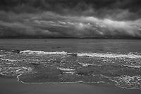Vågor mot sandstrand i molnigt väder på Österlen isvartvitt
