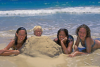 Teenage girls and younger brother playing in the sand near the ocean.