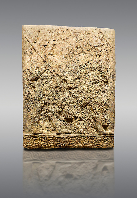 Picture & image of Hittite sculpted orthostats panels of Long Wall Limestone, Karkamıs, (Kargamıs), Carchemish (Karkemish), 900-700 B.C. Soldiers. Anatolian Civilisations Museum, Ankara, Turkey<br /> <br /> Figure of two helmeted warriors. They have their shield in their back and their spear in their hand. The prisoner in their front is depicted as small. The lower part of the orthostat is decorated with braiding motifs. <br /> <br /> On a gray background.