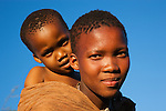 Botswana, Kalahari, bushman (san) mother carrying young child on her back