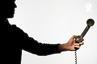 Silhouette of man holding telephone receiver (Licence this image exclusively with Getty: http://www.gettyimages.com/detail/sb10068346bv-001 )