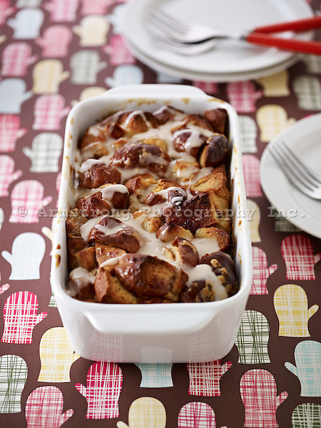 A dish of bread pudding made with leftover raised doughnuts and topped with vanilla icing