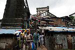 People walk across a bridge in Mabella quarter, Freetown, Sierra Leone, Aug. 15, 2012. Many residents of the impoverished quarter lack access to basic sanitation or drinkable water. Médecins Sans Frontières Belgium, in collaboration with the Sierra Leone Ministry of Health, is running four emergency cholera treatment centers to keep up with the number of patients. Many of the roughly 120 daily patients seen by the MSF team come from extremely impoverished areas of the densely-populated capital, where proper systems for drainage and waste disposal are almost non-existent. Outbreaks of water-borne diseases like cholera become even more likely during the rainy season, which is expected to last at least two more months.