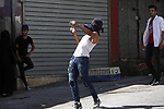 A Palestinian protester hurls stones towards Israeli security forces during clashes in the West Bank city of Hebron on July 13, 2018. Photo by Wisam Hashlamoun