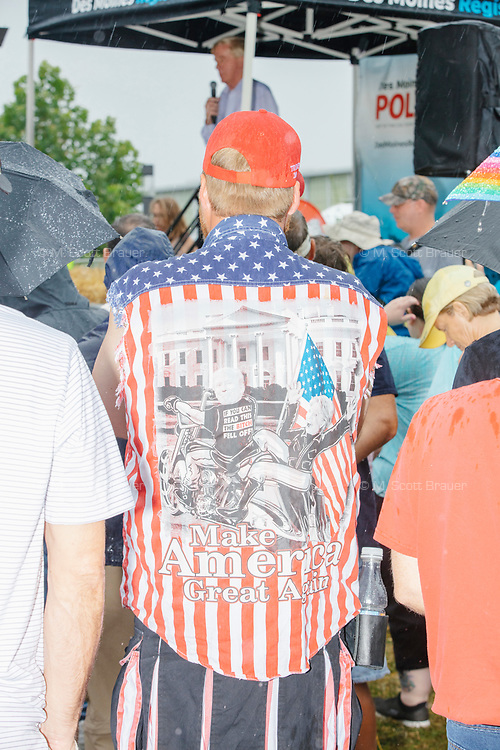 A man wears a pro-Trump, anti-Hillary shirt as former Mass. governor Bill Weld, a Republican presidential candidate, speaks at the Political Soapbox on a rainy day at the Iowa State Fair in Des, Moines, Iowa, on Sun., Aug. 11, 2019.