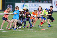 Young fans of the Greenville Drive compete in a tug-of-war between innings of a game on Monday, August 19, 2013, at Fluor Field at the West End in Greenville, South Carolina. (Tom Priddy/Four Seam Images)