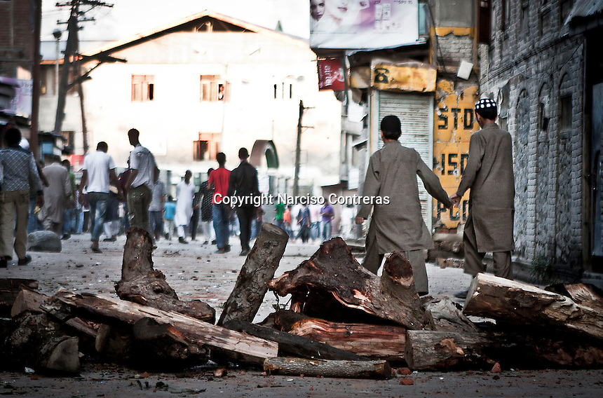 Kashmiri muslim boys crossing through a wood barricade after finished the protest in downtown of Srinagar. Outcry sparks in Nowhatta area against the detention of a kashmiri boy by police.