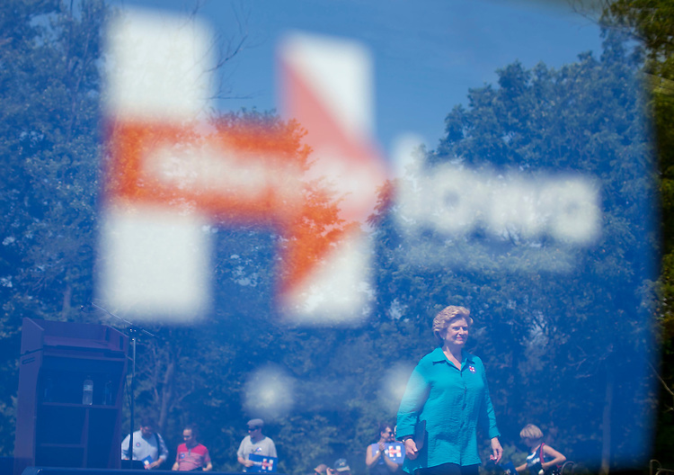 UNITED STATES - August 16: Sen. Debbie Stabenow, D-Mich., leaves the stage after speaking to a small crowd as she campaigns for democratic presidential candidate Hillary Clinton at the Scott County Democrats Picnic in the Park in Eldridge, Iowa, on Sunday, August 16, 2015, as reflected in a window. A majority of the crowd left after hearing Sen. Bernie Sanders, D-Vt., speak prior. (Photo By Al Drago/CQ Roll Call)