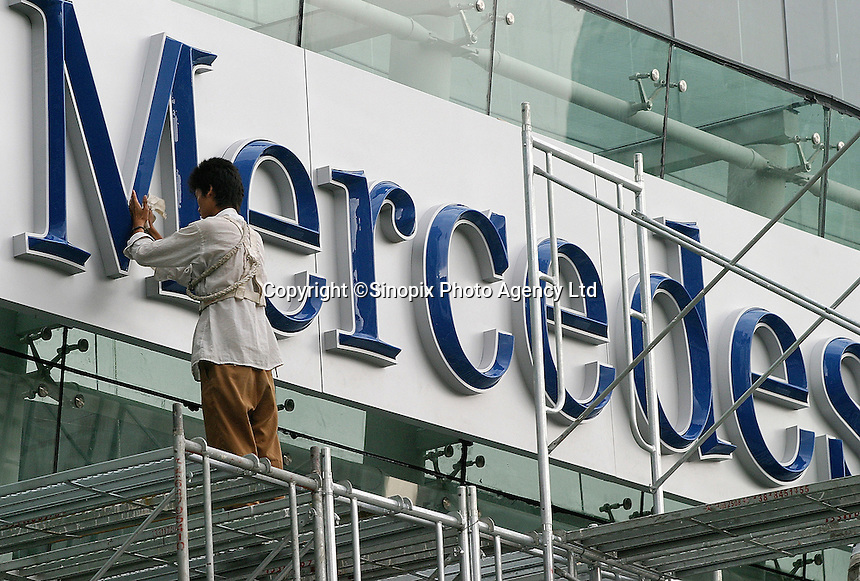 Chinese workers put the finishing touch on a sign out side of a new Mercedes-Benz showroom in Shanghai, China. The German luxury car maker plans to have 50 authorized service centres and showrooms in China by the end of 2004, in hope of continuing its rapidly increasing sales volume in the country. In contrast to the company's sales demographics in western countries, the Chinese auto market seems to be an industry anomaly as a majority of the Mecedes Benz cars sold in China were top of the line S Class rather than the
