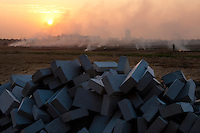 Daytime landscape view of a pile of bricks with an agricultural field burning in the background in Songjiang, China.  © LAN
