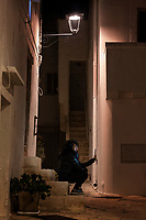 "Italy. Apulia Region. Locorotondo. A lonely young woman seated at night time on a stair takes a selfie with her mobile phone. A selfie is a self-portrait photograph, typically taken with a smartphone which may be held in the hand or supported by a selfie stick. Selfies are often shared on social networking services such as Facebook, Twitter, Snapchat and Instagram. They are for vanity, usually flattering, and are casual in nature (or made to appear casual). ""Selfie"" typically refers to self-portrait photos taken with the camera held at arm's length. Locorotondo is a town and comune with a population of about 14,000. The city is known for its circular structure which is now a historical center, from which derives its name, which means ""Round place"". Apulia (Puglia) is a region in Southern Italy. 5.12.18  © 2018 Didier Ruef"