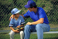 Coach or father gives advice to Little Leaguer