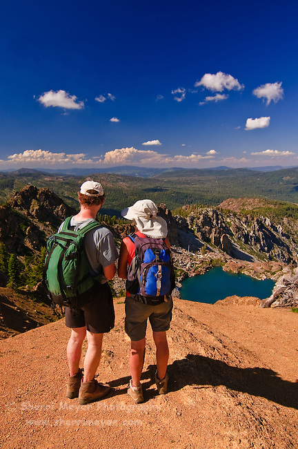 Hikers overlooking Upper Sardine Lake from the Sierra Buttes Fire Lookout Trail, Northern California.