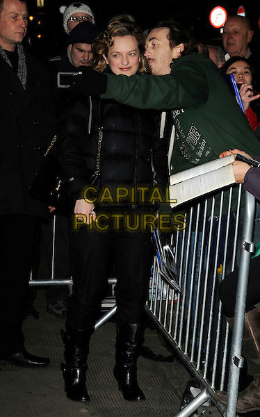 "ELISABETH MOSS .departs after the evening performance of ""The Children's Hour"" at The Comedy Theatre, London, England, UK, 28th January 2011..full length posing with fan black boots trousers puffa puffer coat jacket bag camera photo .CAP/CAN.©Can Nguyen/Capital Pictures."