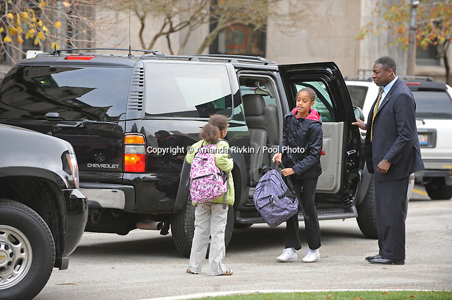 (L-R) Sasha Obama and Malia Obama, daughters of U.S. President Elect Barack Obama, get dropped off for school at the University of Chicago Laboratory School as their dad waits in the car in Chicago, Illinois on Nov. 13, 2008.  Obama is working mostly in the Chicago area as he prepares for his transition to become the 44th U.S. President.