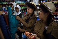 'Twin Teachers' Rian and Rossy shop for cloth at a traditional market in Lampung province to be used as training materials. They'll provide the villagers with training modules to gain practical skills as part of their adult education programme targeted towards women empowerment. Since the early 1990s, twin sisters Sri Rosyati (known as Rossy) and Sri Irianingsih (known as Rian) have used their family inheritance to set up and run 64 schools in different parts of Indonesia, providing primary education combined with practical skills to some of the country's most deprived children.   .