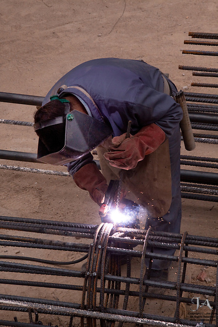 Welder bending over with rebar and bright sparks