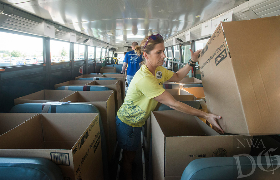 NWA Democrat-Gazette/BEN GOFF @NWABENGOFF<br /> Jamie Blanchard sorts supplies while volunteering with other employees from Ernst &amp; Young in Rogers Friday, Aug. 3, 2018, at the United Way of Northwest Arkansas Fill the Bus drop-off location at the Walmart Supercenter on Pleasant Crossing Boulevard in Rogers. Volunteers are manning busses at ten Walmart Supercenter locations in Northwest Arkansas and Pineville, Mo. from 9:00 a.m. to 3:30 p.m. Friday and Saturday to sort donated school supplies. The donations will go directly to the district the Walmart location is in. Over the past ten years, the annual drive has helped more than 35,000 students in 12 school districts get the supplies they need to start the school year.