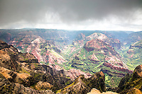 """Waimea Canyon, stormy day.  Waimea Canyon, on Kauai's West Side, is described as """"The Grand Canyon of the Pacific."""" Although not as big or as old as its Arizona cousin, you won't encounter anything like this geological wonder in Hawaii. Stretching 14 miles long, one mile wide and more than 3,600 feet deep, the Waimea Canyon Lookout provides panoramic views of crested buttes, rugged crags and deep valley gorges."""