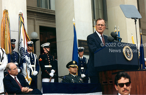 Washington, D.C. - August 15, 1990 -- United States Secretary of Defense Dick Cheney (seated left) and Chairman, Joint Chiefs of Staff, General Colin E. Powell, United States Army (seated center), listen as United States President George H.W. Bush delivers a speech to Pentagon employees, August 15, 1990.  President Bush praised the Defense Department workers for their untiring efforts in support of the deployment of United States military forces to the Middle East -- Operation Desert Shield, and condemned President Saddam Hussein of Iraq for his invasion of Kuwait.  .Credit: White House via CNP