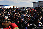 A large crowd waits to board one of the few busses arriving at the Tunisia-Libya border near Ben Guerdane, Tunisia, Friday, Feb. 26, 2011. Thousands of foreign workers continued their exodus across the border into Tunisia, fleeing violence sparked by an uprising against Col Muammar Qaddafi. The refugees, primarily Egyptians, had to wait at the border or at an improvised camp nearby until a bus could take them to the airport in Tunis.