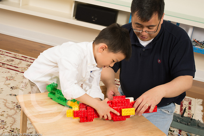 Father working with 6 year old son on ship made from colored plastic building bricks (Duplo) helping him by steadying structure while he adds bricks