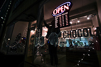 NWA Democrat-Gazette/CHARLIE KAIJO Holiday lights are shown in a window shop reflection, Friday, November 30, 2018 at the downtown square in Bentonville.