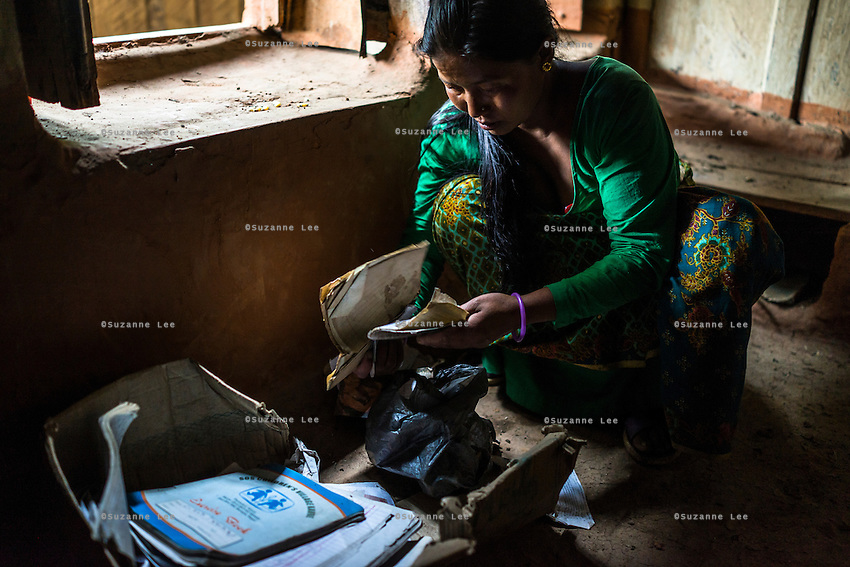 Kalpana Tamang (40), returns to the damaged house where she used to live with her children to collect schooling items in Kavre, Bagmati, Nepal on 30 June 2015.  Kalpana, a widow with 3 children, has been supported by SOS Children's Villages for many years now and had receive the Home-in-a-Box after the earthquake destroyed her house, almost killing her two daughters. She now lives in a temporary shelter, sharing her dwelling with farm animals, and is trying to make ends meet by weaving bamboo baskets to supplement the financial assistance provided by SOS Childrens Villages. The NGO mostly supports her children's welfare and schooling as well as provides her with essential household and schooling items like kitchen utensils and school books and uniforms. Photo by Suzanne Lee for SOS Children's Villages