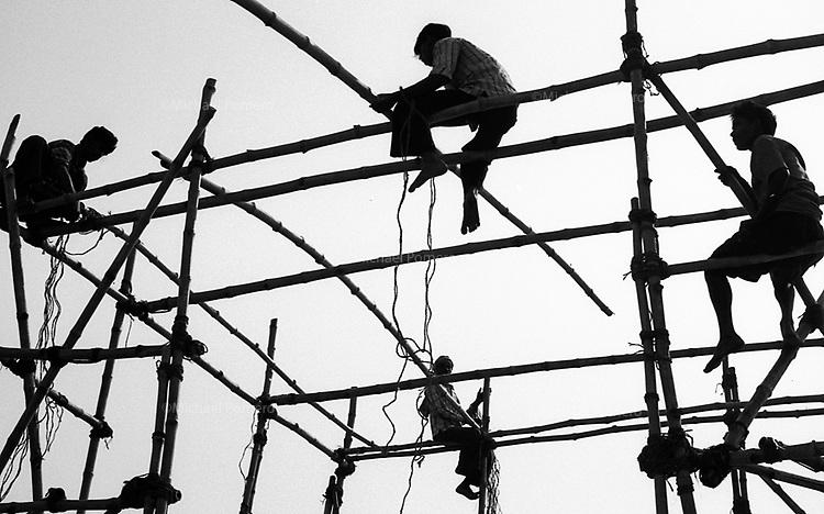 Varanasi (Uttar Pradesh)<br /> <br /> Men on bamboo scaffholding.<br /> <br /> Hommes sur un échafaudage en bambous.