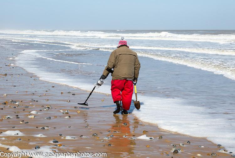 Male  detectorist using metal detector walking along sandy beach Hemsby, Norfolk, England, UK
