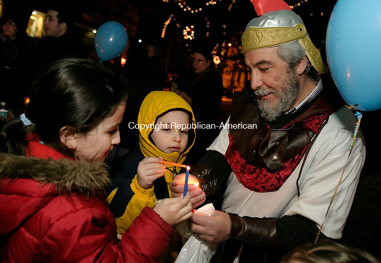 WATERBURY, CT 26 December 2005 -122605BZ01-   <br /> Batya Eisenbach, 8, Nochum Eisenbach, 7, and Alain Levy, dressed as one of the Macabee's, light candles during a menorah lighting on the green in Waterbury Monday night.  The lighting is sponsored by the Chabad Lubavitch of the Northwest Corner.   Levy said the name Macabee refers to  Jewish soldiers.  <br /> Jamison C. Bazinet Republican-American