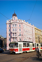An electric tram approaches a transit stop in front of   elaborate buildings of traditional design the Nove Mesto section of Prague. Prague, Bohemia, Czech Republic.