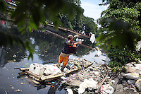 A government worker collects trash from a polluted drainage channel in central Jakarta.  The city's waterways are all heavily <br /> polluted and were recently listed as some of the worst in Asia by the Association of Southeast Asian Nations.
