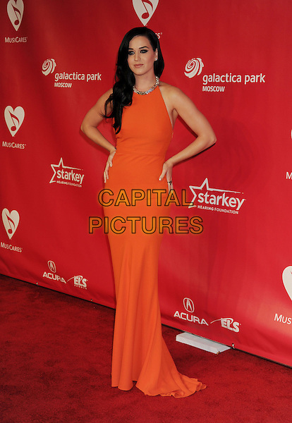 Katy Perry.At the 2013 MusiCares Person Of The Year at Los Angeles Convention Center in Los Angeles, California, USA,.8th February 2013..full length orange dress silver neckline sleeveless hands on hips.CAP/ROT/TM.©Tony Michaels/Roth Stock/Capital Pictures