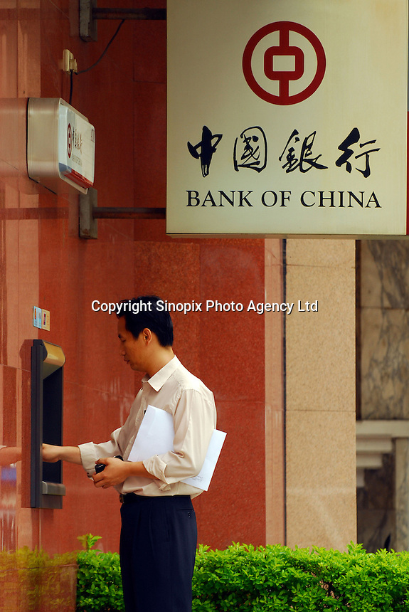 A man withdraws cash from an ATM in Guangzhou, China. China's central recently reaffirmed its commitment to deepen foreign exchange reform to make the yuan more flexible while keeping the currency basically stable.....