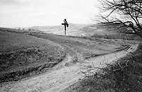 ROMANIA / Maramures / Valeni / April 2003..Cart tracks mark the hilly terrain under a cross which reminds passing villagers to be faithful on their way to and from the fields. ..© Davin Ellicson / Anzenberger..