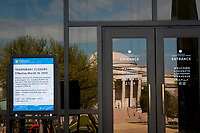 The Smithsonian National Gallery of Art is reflected in the glass doors of the Smithsonian National Air and Space Museum, and a sign is posted to inform people that the museum is closed as the United States deals with the COVID-19 pandemic in Washington, DC, Tuesday, March 17, 2020. Credit: Rod Lamkey / CNP/AdMedia
