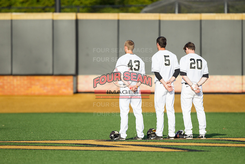 (L-R) Grant Shambley (43), Evan Stephens (5) and Jack Carey (20) stand for the National Anthem prior to the game against the High Point Panthers at Wake Forest Baseball Park on April 2, 2014 in Winston-Salem, North Carolina.  The Demon Deacons defeated the Panthers 10-6.  (Brian Westerholt/Four Seam Images)