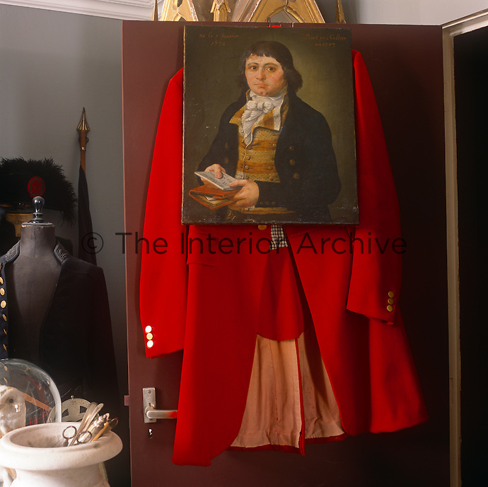 An unframed portrait painting hanging on the back of a door with a red coat underneath.