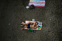 A couple lays together on a public beach on Saturday, Sept. 19, 2015, in Sorrento, Italy. (Photo by James Brosher)