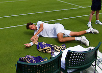 24-06-13, England, London,  AELTC, Wimbledon, Tennis, Wimbledon 2013, Day one, Robin Haase (NED) starts stretching while he is waiting for a treatment by his opponent Mikhail Youzhny (RUS)<br /> <br /> <br /> <br /> Photo: Henk Koster