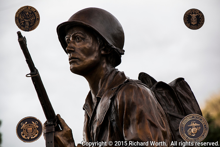 A Veterans Memorial in a city park in Centerville, Utah, features a statue of a soldier on a pedastal with plaques honoring the branches of the U.S. military.